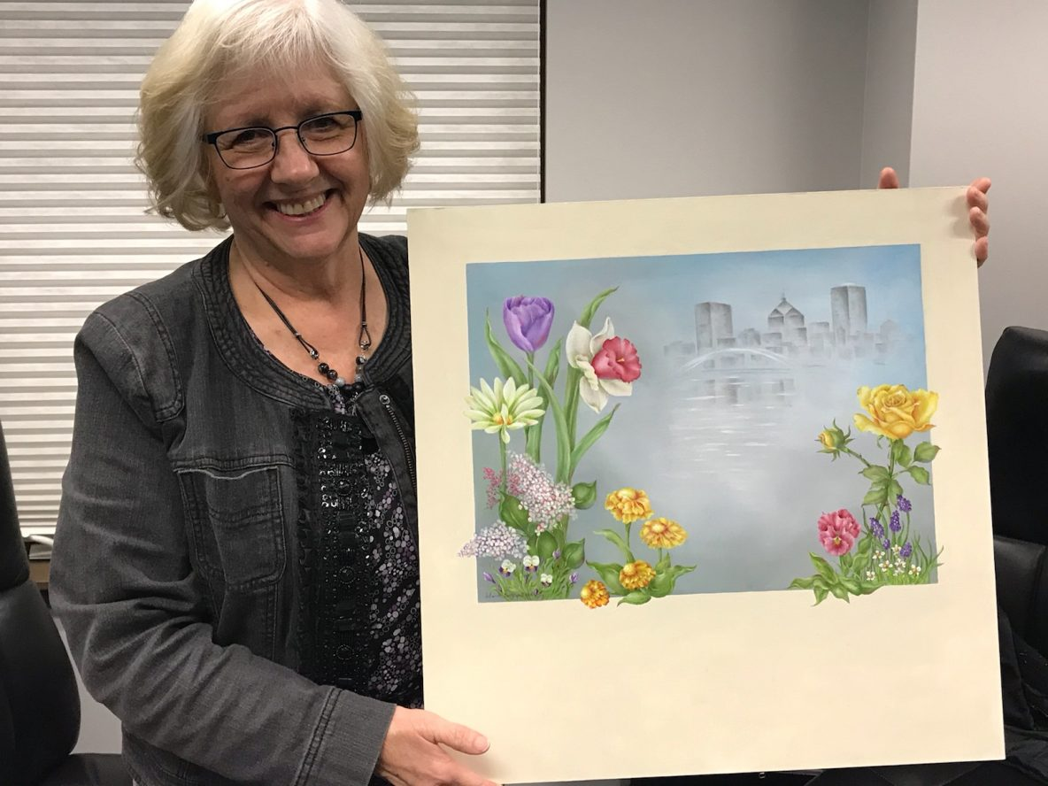 Photo of Deborah Bonnewell holding picture of flowers